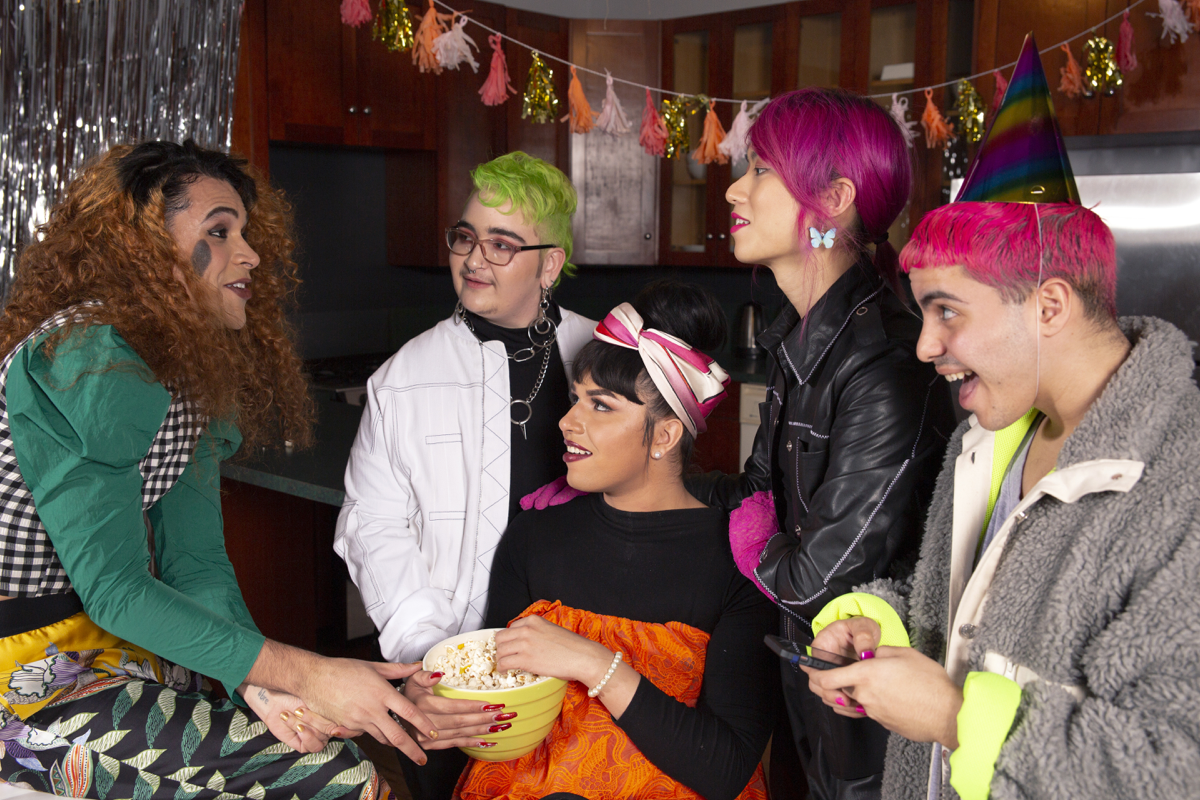 Group of friends of various genders hanging out at a party. One is holding a bowl of popcorn and another is wearing a party hat.