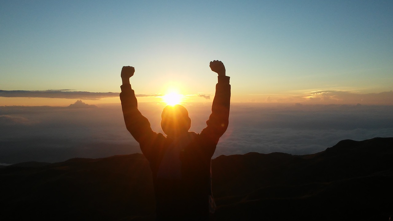 A person with their arms raised facing the sunrise.